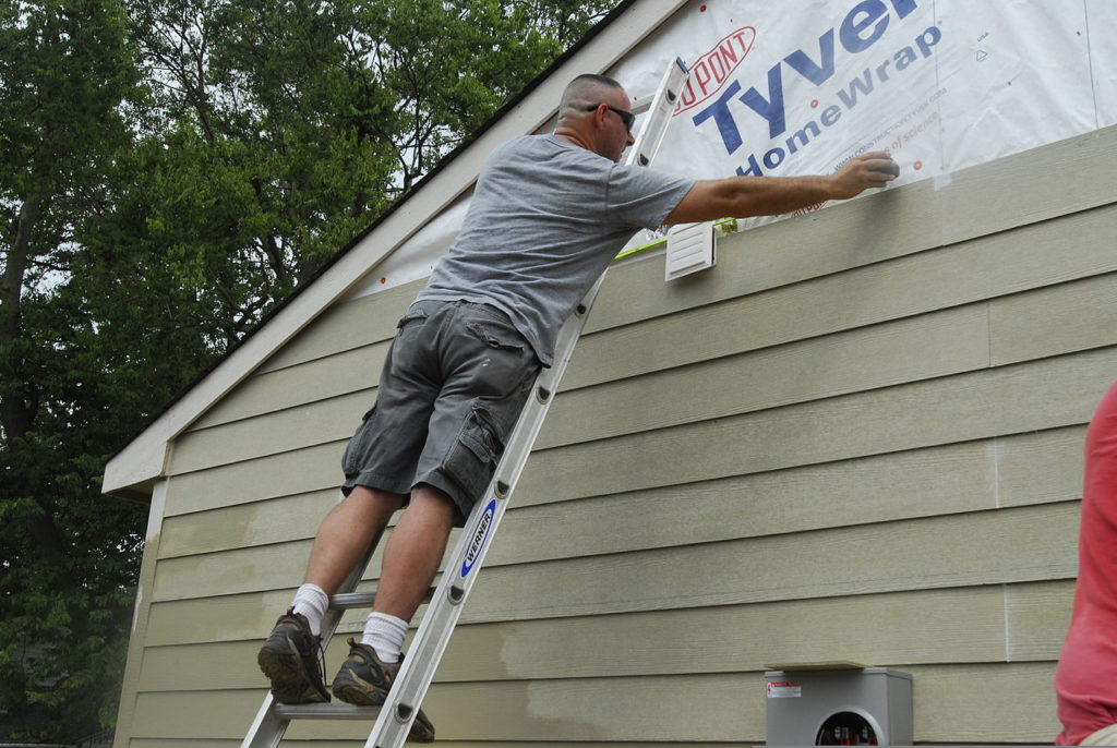 Person installing composite siding in clapboard form