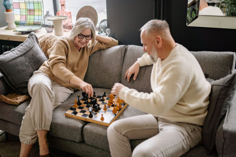 Image showing an elderly couple playing chess on a couch.
